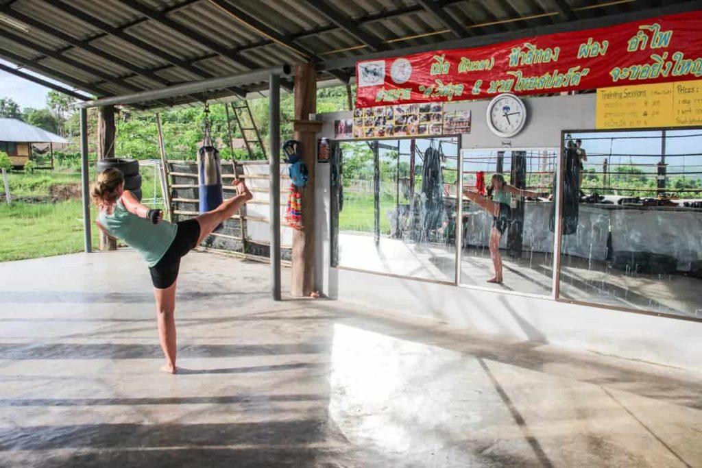Mujer frente al espejo en un gimnasio de boxeo tailandés practicando Muay Thai