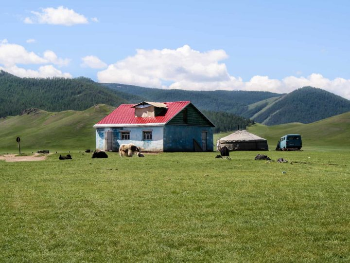 Una casa azul con un techo rojo y un blanco Ger se sienta aislado en el valle de Orkhon de Mongolia